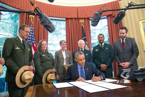 President Barack Obama signs National Monument designations in the Oval Office, July 10, 2015. The three new monuments include Berryessa Snow Mountain in California, Waco Mammoth in Texas, and the Basin and Range in Nevada. Standing behing the President, from left, are: Victor Knox, National Park Service, April Slayton, National Park Service, Interior Secretary Sally Jewell, Chief Tom Tidwell, Randy Moore, Forest Service, and Director Neil Kornze. (Official White House Photo by Amanda Lucidon)